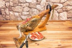 Jambon espagnol de serrano sur la jambe avec le support en bois Images stock