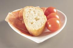 Jambon espagnol sec, jamon, jambon italien, couches coupées avec du pain et tomates-cerises d'un plat en forme de coeur blanc photos stock