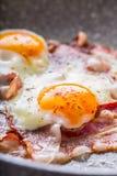 Jambon et oeufs Lard et oeufs faisant frire sur la casserole en céramique Oeuf salé et arrosé avec le poivron rouge Déjeuner angl Photos stock