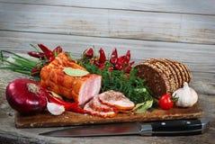Jambon et pain coupés en tranches avec le couteau Légumes verts et rouges sur le cho Images stock