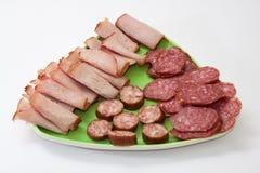 Jambon fumé et saucisse faite maison coupés en tranches et servis d'un plat Images stock