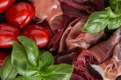 Jambon mix. Ham. Traditional Italian and Spanish salting, smoking, dry-cured dish - jamon Serrano and prosciutto crudo. Sliced with herbs and tomatos on dark Royalty Free Stock Images