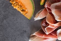 Jambon mix. Ham. Traditional Italian and Spanish salting, smoking, dry-cured dish - jamon Serrano and prosciutto crudo. Sliced with melon on grey background Royalty Free Stock Photography