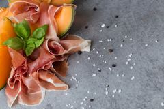 Jambon mix. Ham. Traditional Italian and Spanish salting, smoking, dry-cured dish - jamon Serrano and prosciutto crudo. Sliced with melon on grey background Stock Images