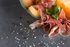 Jambon mix. Ham. Traditional Italian and Spanish salting, smoking, dry-cured dish - jamon Serrano and prosciutto crudo. Sliced with melon on grey background Royalty Free Stock Photo