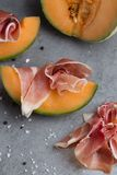 Jambon mix. Ham. Traditional Italian and Spanish salting, smoking, dry-cured dish - jamon Serrano and prosciutto crudo. Sliced with melon on grey background Stock Photo