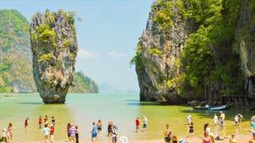 James Bond island (Ko Tapu). Many tourists on the shore between the rocks on the limestone isla Stock Images