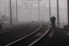 James dean walk. Forlorn figure walks on misty railway line Stock Image