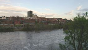 The James River Flows Quietly by Downtown City Skyline and Buildings of Lynchburg Virginia. The sun has not hit the city yet at sunrise in Lynchburg Virginia USA stock video footage