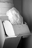 Jammed Garbage In Disposal Bin. A jammed cellophane bag stuck in disposal bin, vertical image in black and white Royalty Free Stock Photo