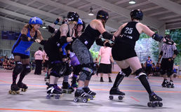 Jammer approaches the pack in roller derby match Stock Image