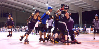 Jammer passes the pack in roller derby match Royalty Free Stock Photo