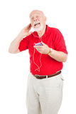 Jamming to the Oldies. Senior man listening to his favorite tunes on a new mp3 player.  Isolated on white Stock Photo