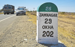 Jamnagar direction milestone State Hig. Horizontal color landscape of the 29 kilometers to Jamnagar direction milestone of the Gujarat state highway in India Stock Photos