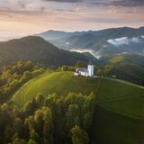 Jamnik,斯洛文尼亚-鸟瞰图圣Primoz在Jamnik附近的斯洛文尼亚和Bled教会和美丽的云彩和朱利安阿尔卑斯山 免版税库存照片