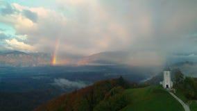 Jamnik, Σλοβενία - πανοραμική άποψη του ουράνιου τόξου πέρα από την εκκλησία του ST Primoz απόθεμα βίντεο