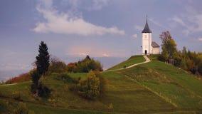 Jamnik, Словения - вид с воздуха радуги над церковью St Primoz в Словении около Jamnik с красивыми облаками и юлианское a видеоматериал