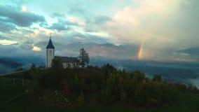 Jamnik, Словения - панорамный вид радуги над церковью St Primoz видеоматериал