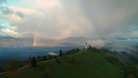 Jamnik, Словения - панорамный вид радуги над церковью St Primoz сток-видео