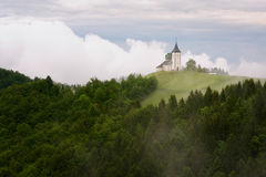 Jamnik church on a hillside in the spring, foggy weather at sunset in Slovenia, Europe. Mountain landscape shortly after spring ra Royalty Free Stock Photos
