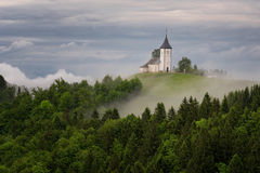 Jamnik church on a hillside in the spring, foggy weather at sunset in Slovenia, Europe. Mountain landscape shortly after spring ra Royalty Free Stock Photo