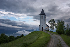 Jamnik church on a hillside in the spring, foggy weather at sunset in Slovenia, Europe. Mountain landscape shortly after spring ra Stock Photo