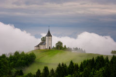 Jamnik church on a hillside in the spring, foggy weather at sunset in Slovenia, Europe. Mountain landscape shortly after spring ra Royalty Free Stock Photography