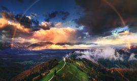 Jamnik, Slovenia - Aerial view of rainbow over the church of St. Primoz in Slovenia near Jamnik with beautiful clouds and Julian. Alps at background stock photos