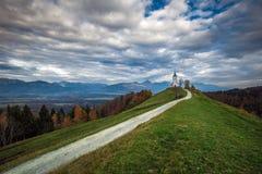 Jamnik, Slovenia - The beautiful church of St. Primoz in Slovenia near Jamnik with beautiful clouds stock images