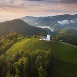 Jamnik Slovenien - flyg- sikt kyrkan av St Primoz i Slovenien nära Jamnik och Bled med härliga moln och Julian Alps royaltyfria foton