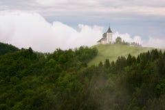 Jamnikkerk op een helling in de lente, mistig weer bij zonsondergang in Slovenië, Europa Berglandschap kort na de lentera Royalty-vrije Stock Foto's