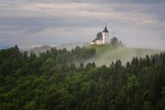 Jamnikkerk op een helling in de lente, mistig weer bij zonsondergang in Slovenië, Europa Berglandschap kort na de lentera Royalty-vrije Stock Afbeeldingen