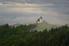 Jamnikkerk op een helling in de lente, mistig weer bij zonsondergang in Slovenië, Europa Berglandschap kort na de lentera Stock Fotografie