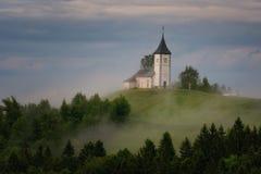 Jamnikkerk op een helling in de lente, mistig weer bij zonsondergang in Slovenië, Europa Berglandschap kort na de lentera Stock Foto's