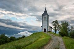 Jamnikkerk op een helling in de lente, mistig weer bij zonsondergang in Slovenië, Europa Berglandschap kort na de lentera Stock Foto