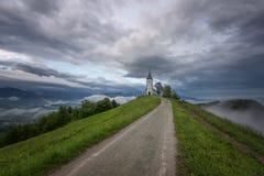 Jamnikkerk op een helling in de lente, mistig weer bij zonsondergang in Slovenië, Europa Berglandschap kort na de lentera Stock Afbeelding