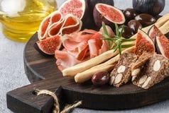 jamon、蒜味咸腊肠、面包条、卡拉迈橄榄和无花果开胃菜  库存照片