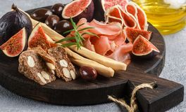 jamon、蒜味咸腊肠、面包条、卡拉迈橄榄和无花果开胃菜  库存图片