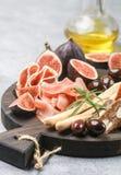 jamon、蒜味咸腊肠、面包条、卡拉迈橄榄和无花果开胃菜  免版税库存照片