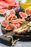 jamon、蒜味咸腊肠、面包条、卡拉迈橄榄和无花果开胃菜  免版税库存图片