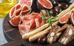 jamon、蒜味咸腊肠、面包条、卡拉迈橄榄和无花果开胃菜  图库摄影