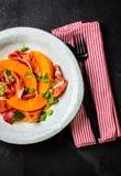 Jamon ветчины, дыня и салат arugula на серой плите стоковая фотография