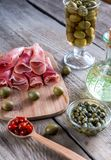 Jamon with capers and olives on the wooden board Stock Photo