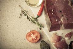 Jamon con las hierbas y especias, sal, aceite de oliva y tomates en sto Foto de archivo
