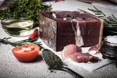 Jamon con las hierbas y especias, sal, aceite de oliva y tomates en sto Fotografía de archivo