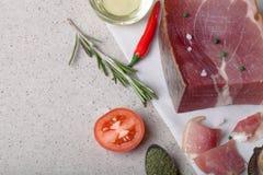 Jamon con las hierbas y especias, sal, aceite de oliva y tomates en sto Fotos de archivo libres de regalías