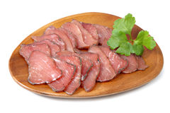 Jamon cured pork meat sliced on wooden plate, over white. Stock Image