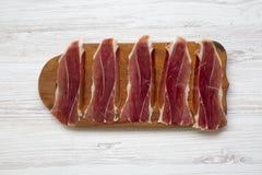 Jamon découpé en tranches Serrano ou Iberico sur couper le conseil en bois Hamon espagnol traditionnel sur le fond en bois blanc, Photo stock
