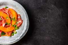 Jamon do presunto, melão e salada da rúcula na placa cinzenta fotos de stock royalty free