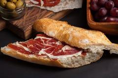 Jamon Iberico用白面包、橄榄在牙签和果子在黑暗的背景 免版税库存图片